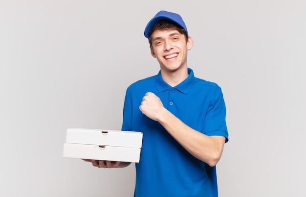 Jonge pizza bezorgt jongen die zich gelukkig, positief en succesvol voelt, gemotiveerd wanneer hij voor een uitdaging staat of goede resultaten viert