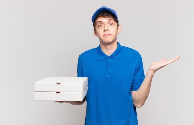 Jonge pizza bezorgt jongen die zich verward en verward voelt, twijfelt, weegt of verschillende opties kiest met grappige uitdrukking