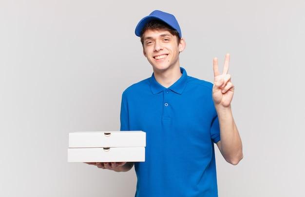 Jonge pizzabezorger die lacht en er vriendelijk uitziet, nummer twee of seconde toont met de hand naar voren, aftellend