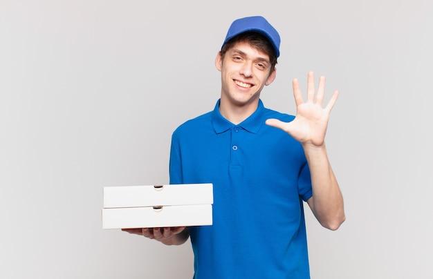 Jonge pizzabezorger die lacht en er vriendelijk uitziet, nummer vijf of vijfde toont met de hand naar voren, aftellend