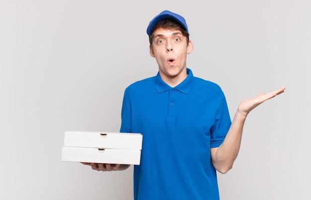 Jonge pizzabezorger die verrast en geschokt kijkt, met open mond terwijl hij een object vasthoudt met een open hand aan de zijkant