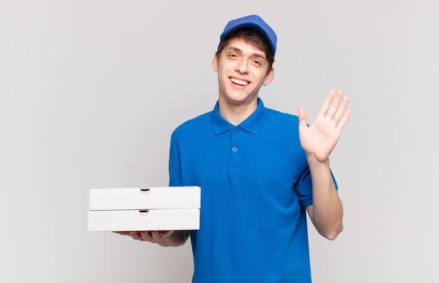 Jonge pizzabezorger die vrolijk en vrolijk lacht, met de hand zwaait, je verwelkomt en begroet, of afscheid neemt