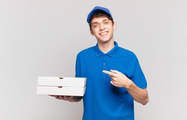 Jonge pizzabezorger die vrolijk lacht, zich gelukkig voelt en naar de zijkant en naar boven wijst, een object in de kopieerruimte laat zien