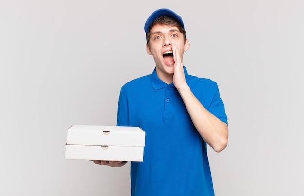 Jonge pizzabezorger die zich gelukkig, opgewonden en positief voelt, een grote schreeuw geeft met de handen naast de mond, roept