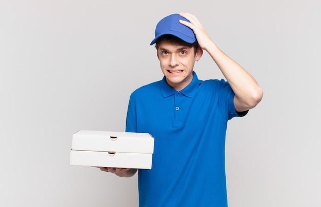 Jonge pizzabezorger die zich gestrest, bezorgd, angstig of bang voelt, met de handen op het hoofd, in paniek bij vergissing