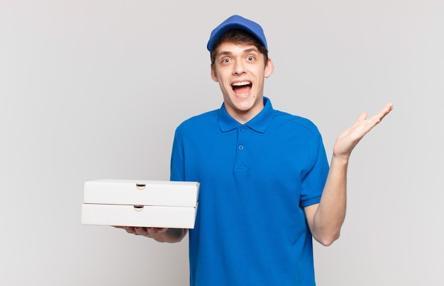 Jonge pizzabezorger voelt zich blij, opgewonden, verrast of geschokt, glimlacht en verbaasd over iets ongelooflijks