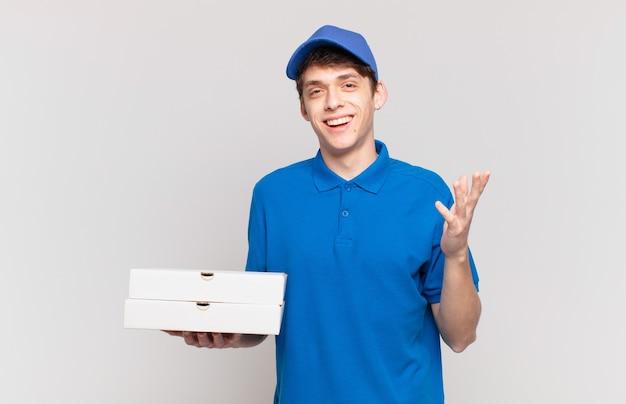 Jonge pizzabezorger voelt zich blij, verrast en opgewekt, glimlacht met een positieve houding en realiseert een oplossing of idee