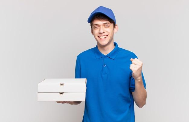 Jonge pizzabezorger voelt zich geschokt, opgewonden en blij, lacht en viert succes en zegt wauw!