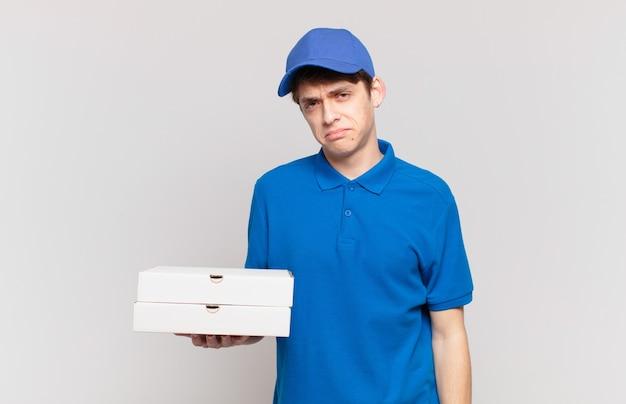 Jonge pizzabezorger voelt zich verdrietig en zeurderig met een ongelukkige blik, huilend met een negatieve en gefrustreerde houding