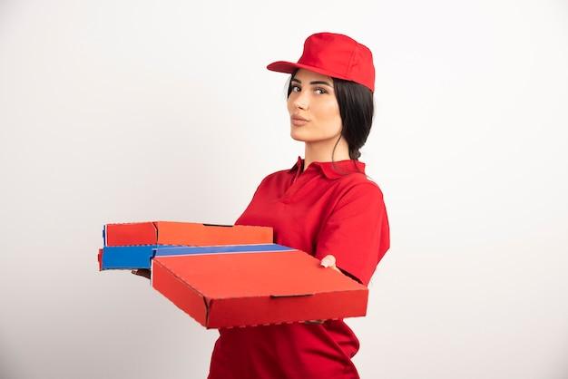 Jonge pizzakoerier vrouw met pizzadozen.