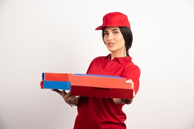 Jonge pizzakoerier vrouw pizza weggeven.