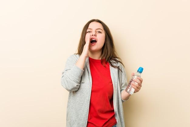Jonge plus grootte bochtige vrouw die een waterfles houdt opgewonden schreeuwen aan voorzijde.