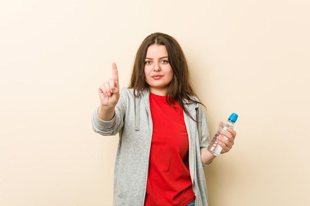 Jonge plus grootte curvy vrouw die een waterfles houdt die nummer één met vinger toont.