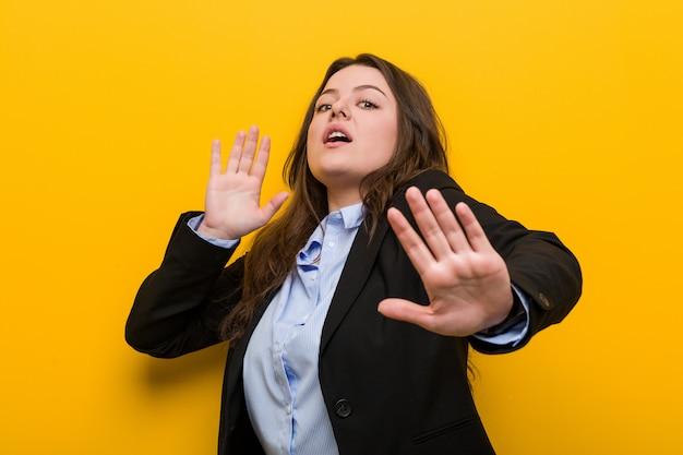Jonge plus grootte kaukasische bedrijfsvrouw die door een dreigend gevaar wordt geschokt