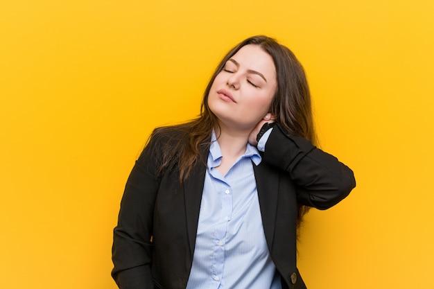 Jonge plus size blanke zakenvrouw die nekpijn lijdt vanwege een zittende levensstijl.