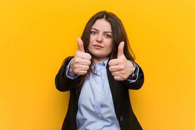 Jonge plus size blanke zakenvrouw met thumbs ups, proost over iets, steun en respect.