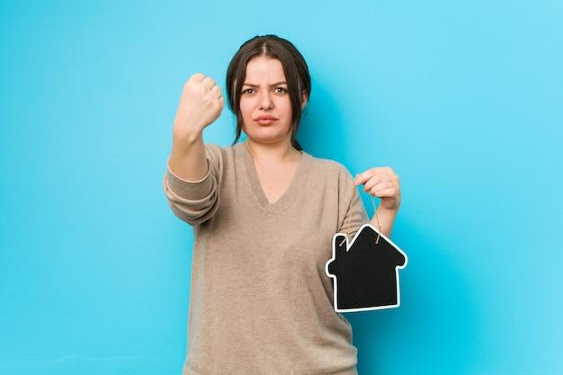 Jonge plus size bochtige vrouw met een huispictogram met vuist, agressieve gezichtsuitdrukking.