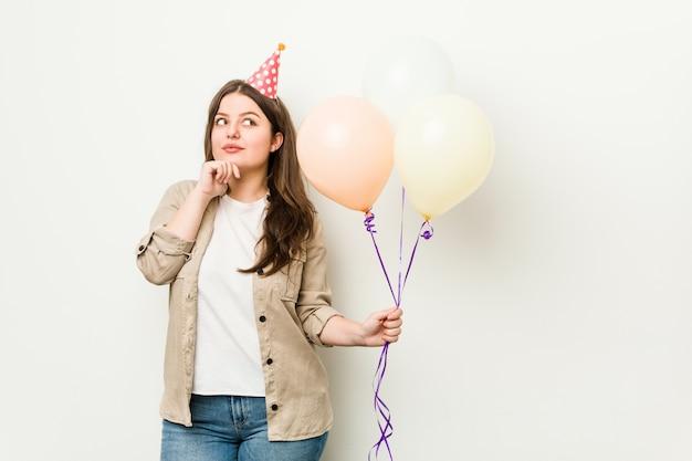 Jonge plus size bochtige vrouw viert een verjaardag zijwaarts op zoek met twijfelachtige en sceptische uitdrukking.