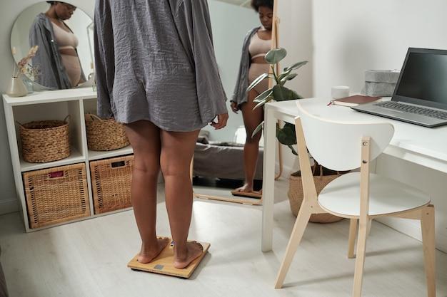 Jonge plus size vrouw in grijs shirt staande op schalen