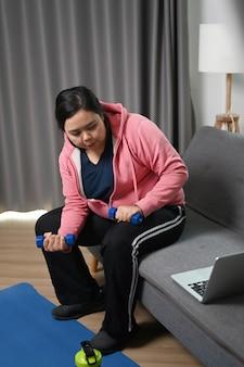 Jonge plus size vrouw kijken tutorial online training en oefeningen thuis doen.