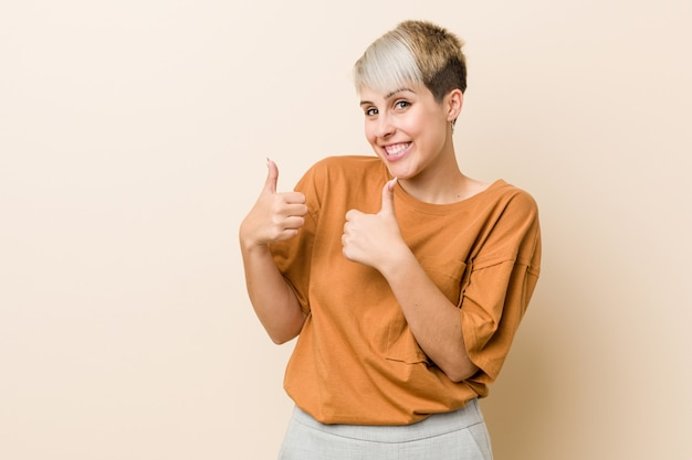 Jonge plus size vrouw met kort haar beide duimen omhoog, glimlachen en zelfverzekerd.