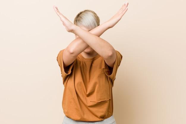 Jonge plus size vrouw met kort haar houden twee armen gekruist, ontkenning concept.