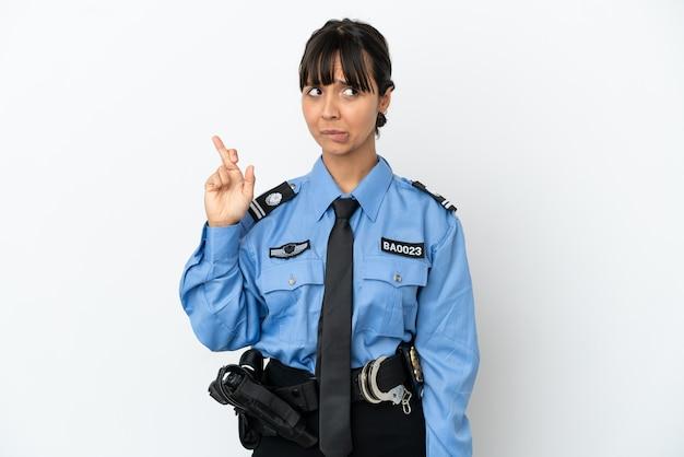 Jonge politie gemengd ras vrouw geïsoleerde achtergrond met vingers die kruisen en het beste wensen