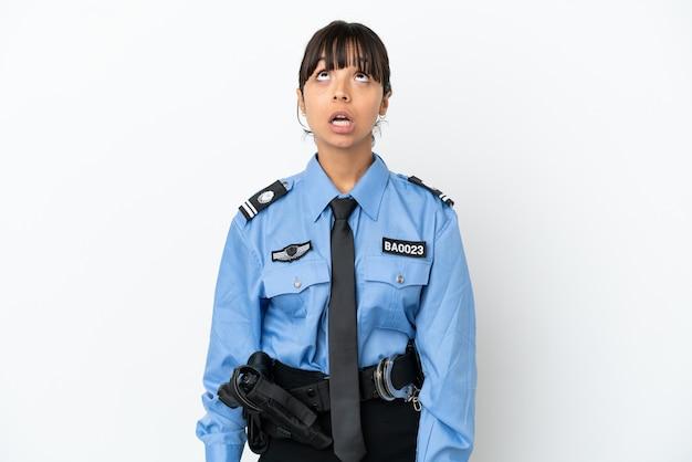 Jonge politie gemengd ras vrouw geïsoleerde achtergrond opzoeken en met verbaasde uitdrukking