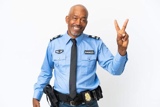 Jonge politie man geïsoleerd op een witte achtergrond glimlachend en overwinning teken tonen