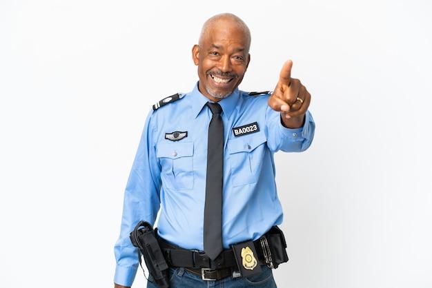 Jonge politie man geïsoleerd op een witte achtergrond verrast en wijzend naar voren