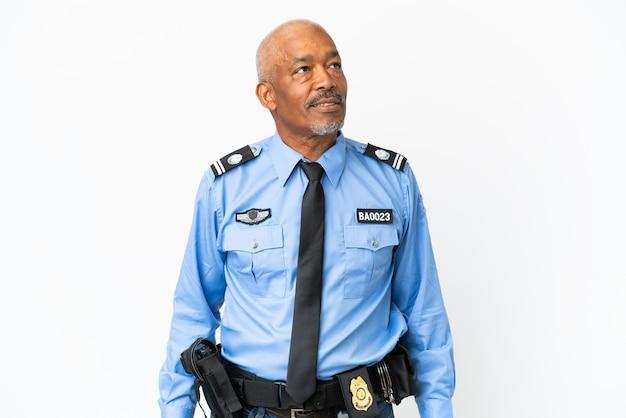 Jonge politieman geïsoleerd op een witte achtergrond die een idee denkt terwijl hij omhoog kijkt