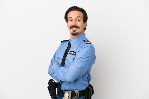 Jonge politieman over geïsoleerde achtergrond wit met gekruiste armen en blij