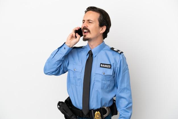 Jonge politieman over geïsoleerde witte achtergrond die een gesprek voert met de mobiele telefoon