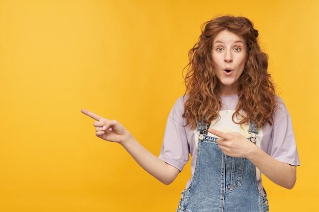Jonge positief verbaasde gembervrouw, draagt een blauwe denim overall en een paars t-shirt, wijzend met beide handen naar de kopieerruimte opzij, met een geschokte gezichtsuitdrukking. geïsoleerd over gele muur
