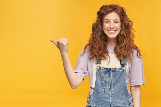 Jonge positieve gembervrouw, draagt blauwe overall en paars t-shirt, glimlacht breed, geeft met duim aan op kopieerruimte