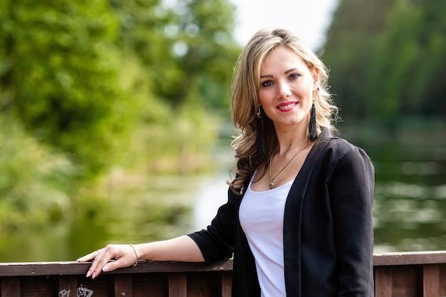Jonge positieve, glimlachende vrouw die bij de houten balustrades van de pier staat, wazig meerlandschap op de achtergrond