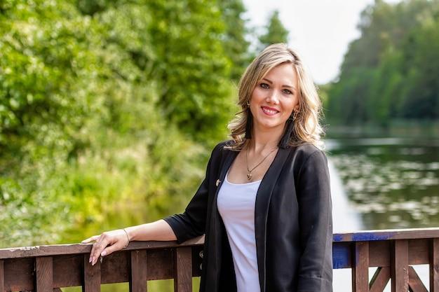 Jonge positieve, glimlachende vrouw die zich bij de houten balustrades van de pier, wazig meerlandschap bevindt