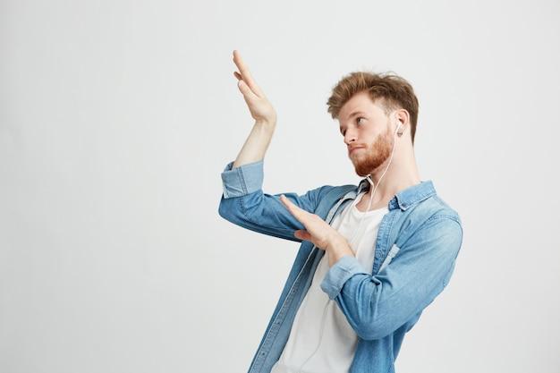 Jonge positieve knappe mens die in hoofdtelefoons aan muziek het dansen bewegen luisteren.