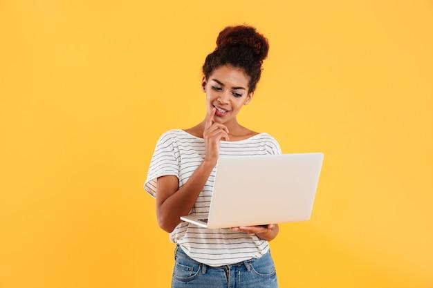Jonge positieve koele dame met krullend haar dat geïsoleerde laptop met behulp van