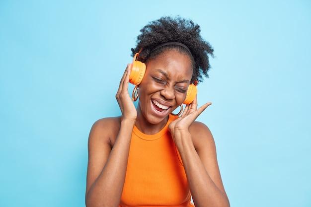 Jonge positieve krullende afro-amerikaanse vrouw luistert graag naar muziek in een draadloze stereohoofdtelefoon