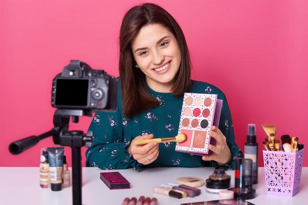 Jonge positieve lachende europese schoonheid vlogger zittend aan tafel tegen camera en presenteert oogschaduw palet