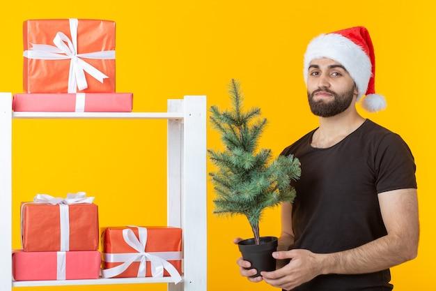 Jonge positieve man met een baard en kerstman hoed staat in de buurt van stand met geschenken en kerstboom op gele achtergrond. concept van felicitatie cadeau en kortingen voor kerstmis en nieuwjaar.