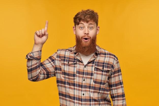 Jonge positieve man, met grote rode baard, kijkt in de camera met geschokte gezichtsuitdrukking, wijst met een vinger naar boven en heeft een nieuw idee voor opstarten