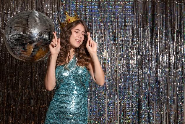 Jonge positieve mooie dame blauw groene glanzende jurk met pailletten met kroon dragen in het feest