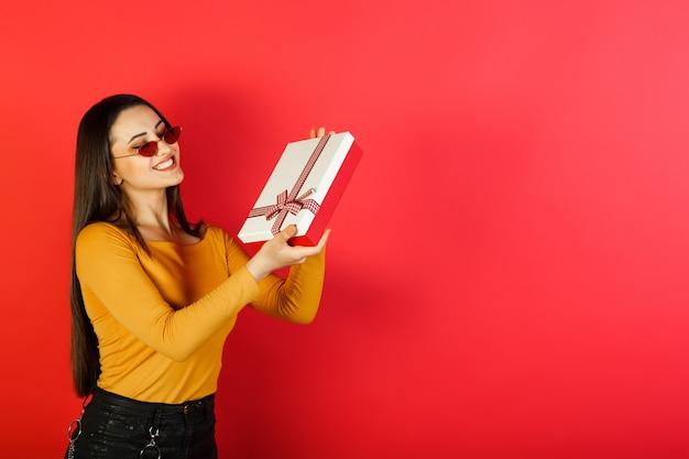 Jonge positieve mooie vrouw die in stijlvolle kleding vakantiegift op rode achtergrond houdt.