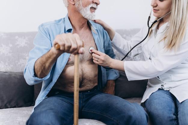 Jonge positieve verzorger die zorgt voor senior man in verpleeghuis.
