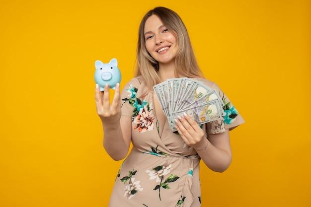 Jonge positieve vrouw met een blauw spaarvarken en dollarbiljetten in haar hand op een gele achtergrond
