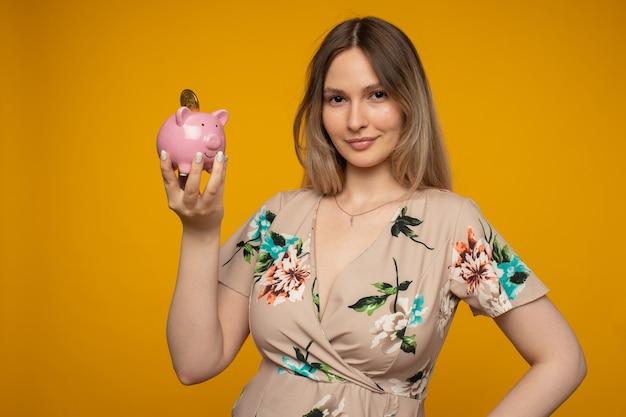 Jonge positieve vrouw met een roze spaarvarken en bitcoin in haar hand op een gele achtergrond