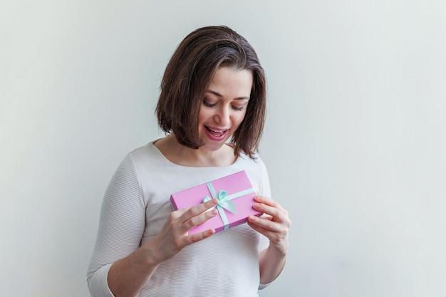 Jonge positieve vrouw met kleine roze geschenkdoos geïsoleerd op wit kijken blij en opgewonden