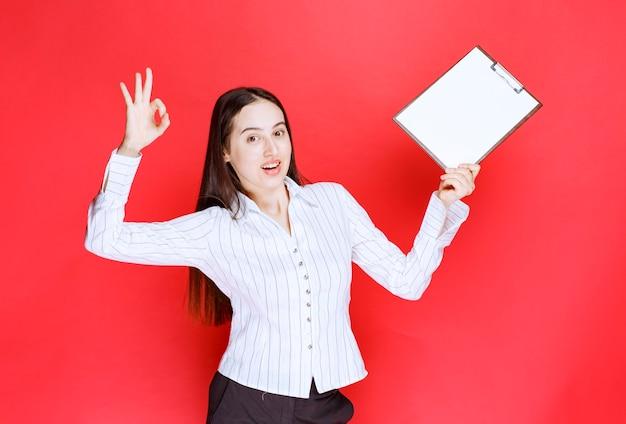 Jonge positieve zakenvrouw die leeg klembord houdt en ok teken geeft.